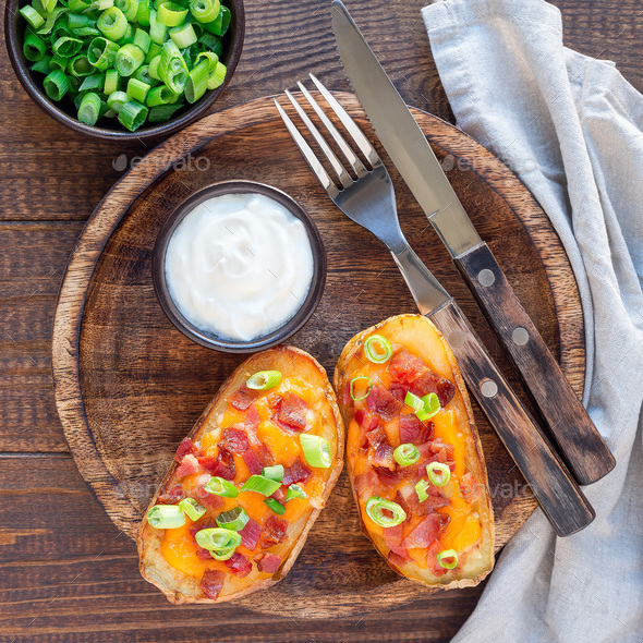 Baked loaded potato skins with cheddar cheese and bacon, garnish - Stock Photo - Images