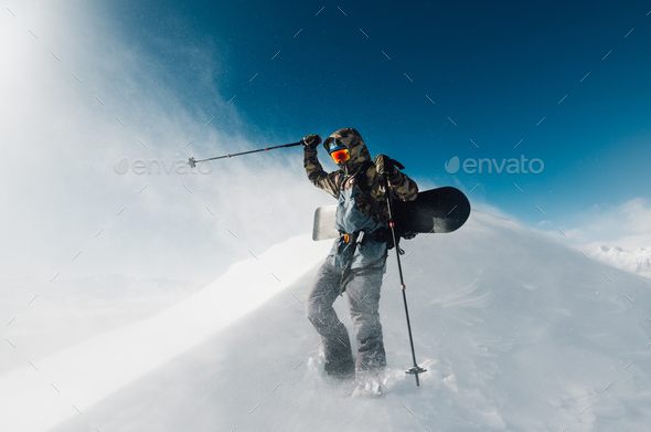 sportsman go with snowboard equipment in the snowstorm - Stock Photo - Images