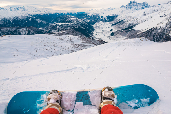 snowboarder with snowboard is sitting on the mountain - Stock Photo - Images