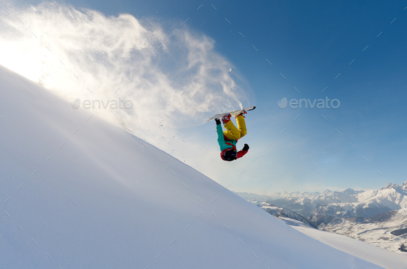 girl snowboarder jumping front flip leaving a wave of snow - Stock Photo - Images