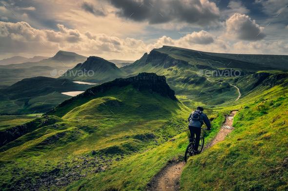Mountain biker riding through rough mountain landscape of Quiraing, Scotland - Stock Photo - Images