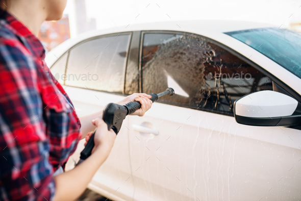 Female person wash off the foam from the car glass - Stock Photo - Images