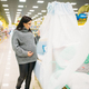 Pregnant woman choosing baby cot in store - PhotoDune Item for Sale