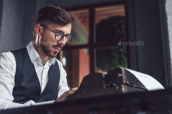 Working man with a retro typewriter - Stock Photo - Images
