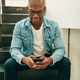 Young African businessman sitting on office stairs reading text messages - PhotoDune Item for Sale
