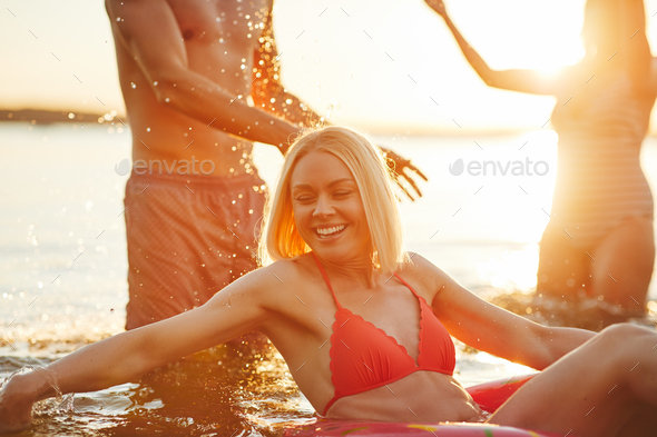 Smiling young woman and friends splashing water in a lake - Stock Photo - Images
