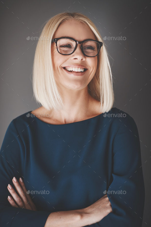 Smiling businesswoman standing with arms crossed against a gray background - Stock Photo - Images
