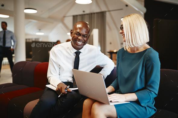 Two coworkers laughing together while sitting on an office soafa - Stock Photo - Images