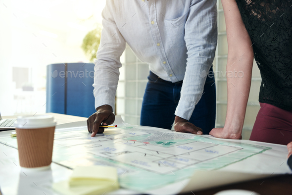 Architects discussing blueprints together at table in an office - Stock Photo - Images