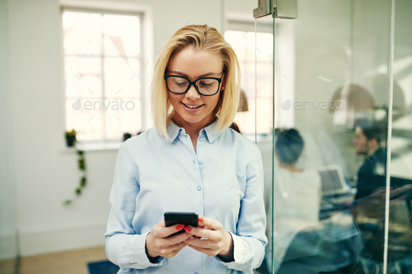 Smiling businesswoman standing in an office using a cellphone - Stock Photo - Images
