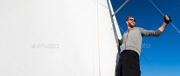 Yacht captain with a beard stands on sail boom on a sailing yacht, holding the rope in his hand and - Stock Photo - Images