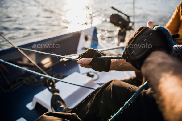 Close-up of male hands in gloves pulling rope of sailboat while mooring yacht and sitting with - Stock Photo - Images