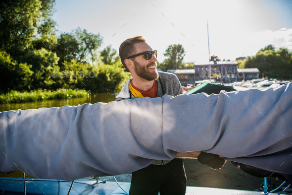 Young sailor in sunglasses holds and moves main sail with both hands. He is happy and smiling. Young - Stock Photo - Images