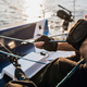 Close-up of male hands in gloves pulling rope of sailboat while mooring yacht and sitting with - PhotoDune Item for Sale