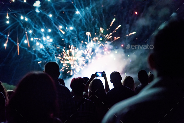 Crowd watching fireworks and celebrating new year - Stock Photo - Images