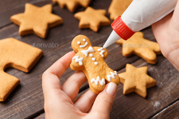 Confectioner decorating gingerman with royal icing, closeup - Stock Photo - Images