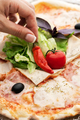 Hand decorates delicious homemade Italian pizza with pepper - PhotoDune Item for Sale