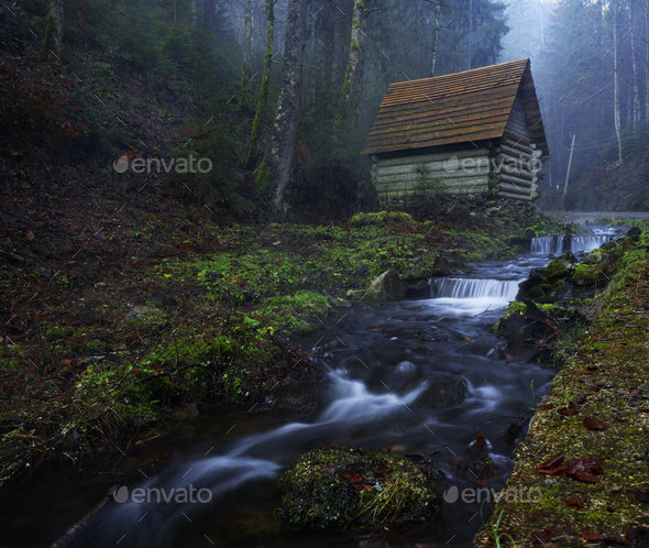 Small house stands on the banks of a mountain river - Stock Photo - Images
