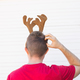 Christmas, holidays and people concept - a man's head with deer horns on it. Man scratches his - PhotoDune Item for Sale