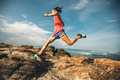 Young fitness woman trail runner running to rocky mountain top on seaside - PhotoDune Item for Sale