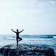 Yoga Woman outstretched arms at seaside mossy coral reef - PhotoDune Item for Sale
