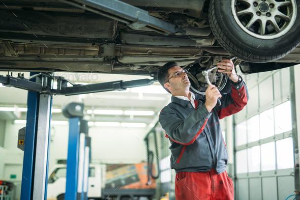 Auto mechanic working in garage. Repair service - Stock Photo - Images