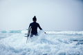 Surfer with surfboard  in the waves - PhotoDune Item for Sale