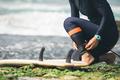 Surfer tying leg leash before surfing - PhotoDune Item for Sale
