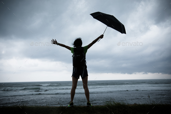 2cac1e9965771 woman with umbrella in the storm seaside Stock Photo by lzf   PhotoDune