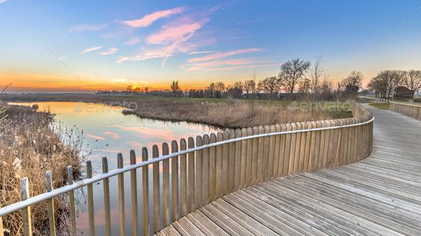 Plankied balustrade sunset over swamp - Stock Photo - Images