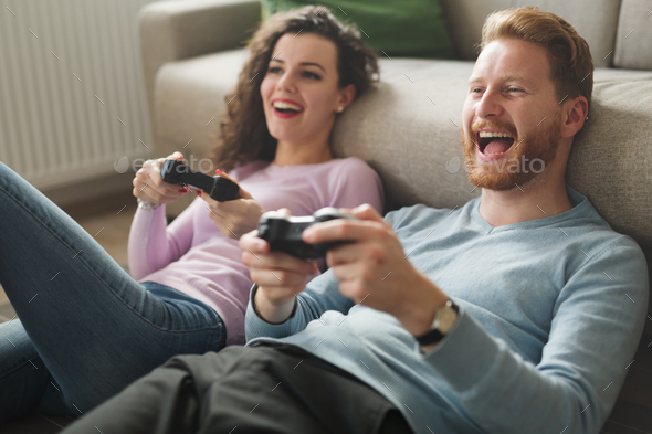 Beautiful couple playing video games on console - Stock Photo - Images