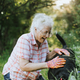 Senior woman petting her dog in the garden - PhotoDune Item for Sale