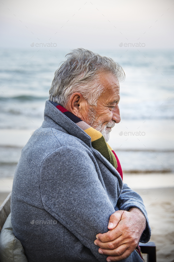 Mature man sitting on a chair by the seashore - Stock Photo - Images