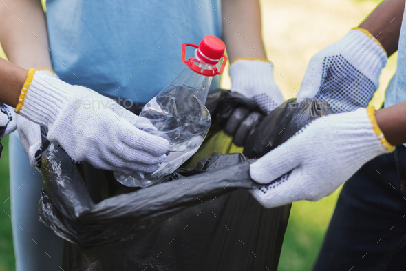 Volunteers collecting recyclable plastic bottles in park - Stock Photo - Images
