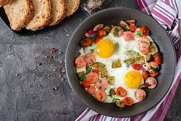 Frying pan with tasty cooked egg, sausages and vegetables on grey table. Breakfast. Top view - Stock Photo - Images