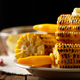 Wooden table with deep grilled sweet corn cobs under melting but - PhotoDune Item for Sale