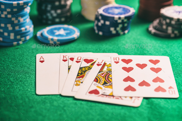 Casino, gambling concept. Hearts royal flush cards and poker chips on green  felt Stock Photo by rawf8