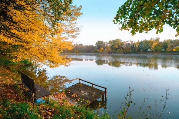 Autumn foliage lake in morning with pier - Stock Photo - Images