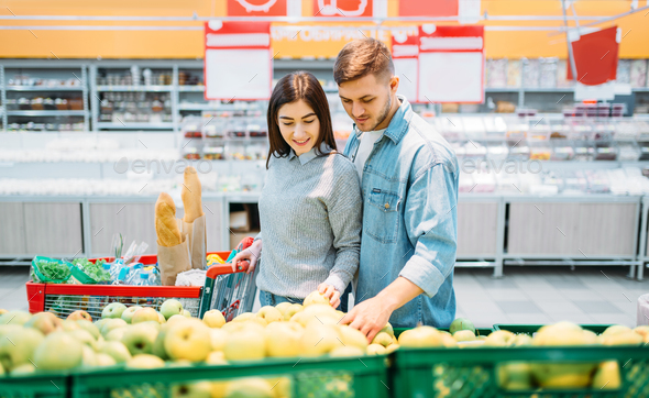 Couple With Cart Choosing Apples In A Supermarket