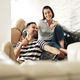 Happy Hispanic Couple Using Smartphones On Couch At Home - PhotoDune Item for Sale