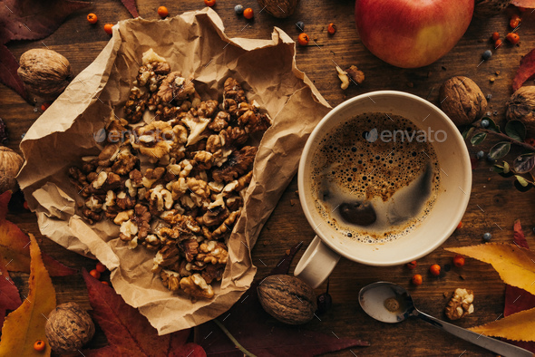 Enjoying fruits of autumn - apple, coffee and walnut on table