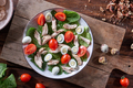 Healthy freshly prepared salad of quail eggs, meat, tomatoes and spinach in a plate on a wooden - PhotoDune Item for Sale