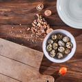 A bowl with quail eggs, pieces of walnut and a wooden board on the kitchen table with copy space - PhotoDune Item for Sale