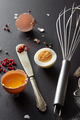Raw and boiled egg, a metal whisk and a knife with red pepper on a black concrete background - PhotoDune Item for Sale