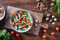 A plate of salad from boiled meat, quail eggs, spinach and tomatoes on a wooden board on the kitchen - PhotoDune Item for Sale