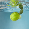 Yellow fresh lemon falling water with a splash on a blue background - PhotoDune Item for Sale