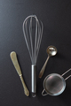 Set of kitchen tools knife, whisk, sieve and spoon on black concrete background with copy space. Top - PhotoDune Item for Sale