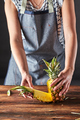 Cut pineapple. Girls hands hold fruit on a brown wooden table with copy space. Ingredient for - PhotoDune Item for Sale