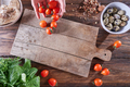 The hands of the woman put ripe tomatoes on a wooden board with quail eggs, pieces of nuts and copy - PhotoDune Item for Sale