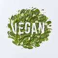 Round composition of different green vegetables with vegan paper lettering on a gray background with - PhotoDune Item for Sale
